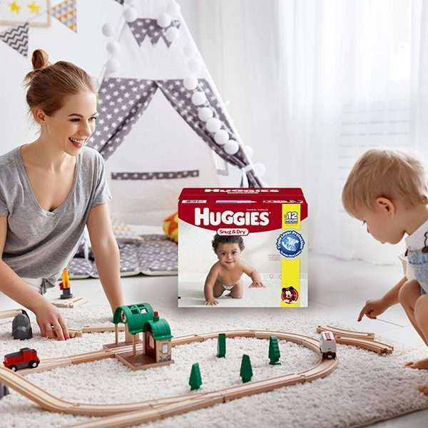 Happy mom playing on floor with trains and baby
