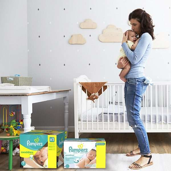 Mom holding baby changing pampers diapers