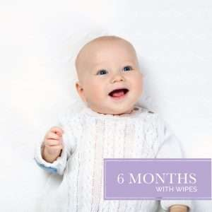 Six months diaper and wipes with smiling baby on blanket