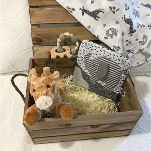 Jungle Baby Crate with white blanket on white bed