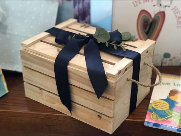 Blue bow brown baby crate with book in background