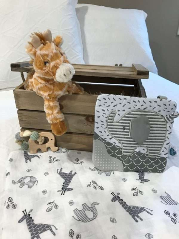 Jungle Baby Crate opened lid on white bed with Jungle baby toys