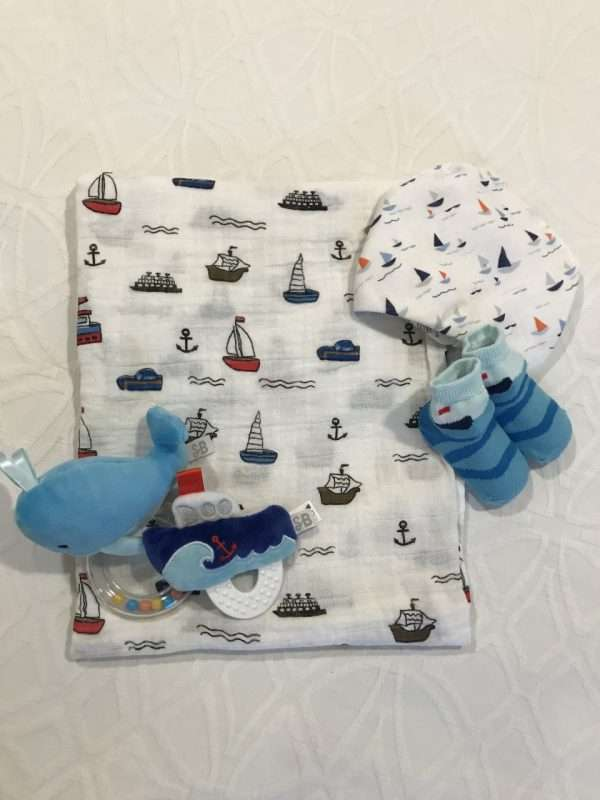 Sailboat baby items on a white sheet