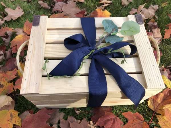 Wooden crate in blue ribbon and leaves