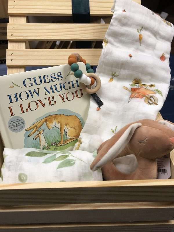 wooden crate with baby swaddle blanket book and toys
